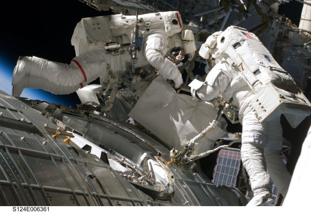 Astronauts Mike Fossum (left) and Ron Garan, undertaking a spacewalk from STS-124 on June 5, 2008, construction and maintenance on the International Space Station. During the seven-hour, 11-minute spacewalk, Fossum and Garan installed television cameras on the front and rear of the Kibo Japanese Pressurized Module (JPM) to assist Kibo robotic arm operations, removed thermal covers from the Kibo robotic arm, prepared an upper JPM docking port for flight day seven's attachment of the Kibo logistics module, readied a spare nitrogen tank assembly for its installation during the third spacewalk, retrieved a failed television camera from the Port 1 truss, and inspected the port Solar Alpha Rotary Joint (SARJ).