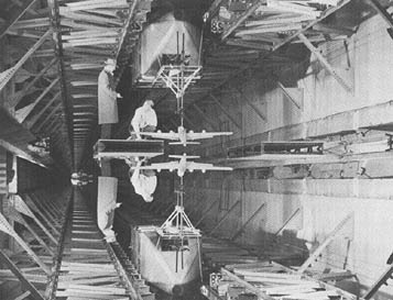 Among the new facilities won by the NACA during World War II was towing tank #2. Here, two workers set up a model for test in the new tank. The illusion that they are, suspended in space was created by printing the photograph upside down.