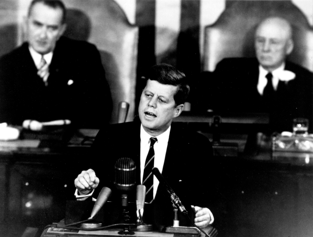 "John F. Kennedy delivering his ""Urgent National Needs"" Speech to a joint session of Congress on May 25, 1961. Among other initiatives, but the one that is most remembered, he said, ""I believe this nation should commit itself, before this decade is out, of landing a man on the Moon and returning him safely to Earth."""