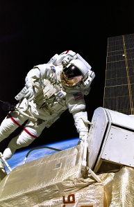 Astronaut Jerry L. Ross, STS-88 mission specialist, is pictured during one of three space walks that were conducted on the twelve-day mission between December 4-15, 1998. Perched on the end of Endeavour's remote manipulator system (RMS) arm, astronaut James H. Newman, mission specialist, recorded this image. Newman can be seen reflected in Ross' helmet visor. The solar array panel for the Russian-built Zarya module can be seen along right edge. This was just the first of about 160 spacewalks totaling 1,920 work-hours required to complete the International Space Station.
