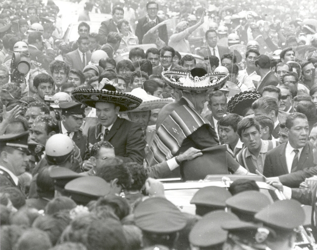 The Apollo 11 astronauts, Neil A. Armstrong, Edwin E. Aldrin, Jr., and Michael Collins, wearing sombreros and ponchos, are swarmed by thousands in Mexico City as their motorcade is slowed by the enthusiastic crowd. The GIANTSTEP-APOLLO 11 Presidential Goodwill Tour emphasized the willingness of the United States to share its space knowledge. The tour carried the Apollo 11 astronauts and their wives to 24 countries and 27 cities in 45 days.