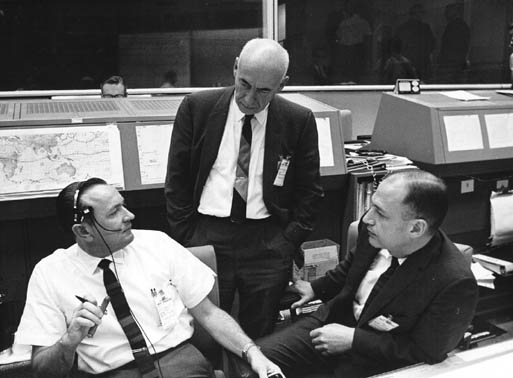 Discussing the scrub of the Gemini VI space flight are (from left), Christopher C. Kraft Jr., Red Team flight director; Dr. Robert R. Gilruth, center director; and George M. Low, deputy director. The three officials monitored the countdown on NASA's Gemini VI from their positions in the MSC Mission Control Center on December 12, 1965. The Gemini VI flight was subsequently rescheduled and launched on December 15, 1965.