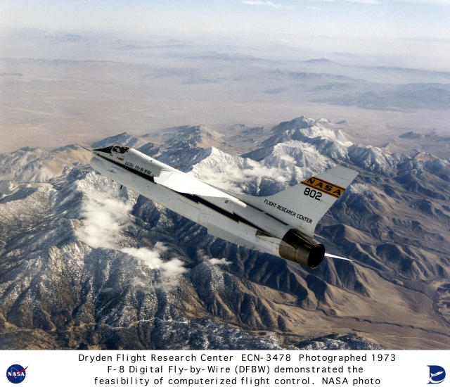 F-8 Digital Fly-by-Wire (DFBW) aircraft in flight over snow capped mountains. Externally identical to a standard Navy F-8C, this aircraft had its control system replaced initially by a primary system using an Apollo digital computer. The backup system used three analog computers. When the pilot moved the airplane's stick and rudder, electronic signals went to the computer, which would generate signals to move the control surfaces. The system was designed so that the digital fly-by-wire aircraft would handle almost identically to a standard F-8C. Later, in Phase 2, the aircraft used three IBM AP-101 computers for its flight control system.