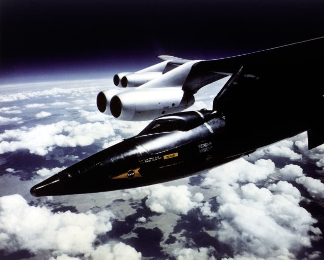 The X-15 research aircraft attached to the B-52 mothership during one of its 199 missions.