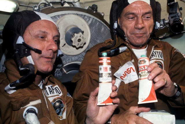 U.S. commander Thomas Stafford and docking module pilot Deke Slayton participate in a toast to a successful docking. The tubes have the labels of famous Russian vodka brands, but actually contained borscht, a beet soup.