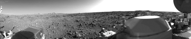 This first panoramic view by Viking 1 from the surface of Mars in 1976 depicts an out of focus spacecraft component toward left center is the housing for the Viking sample arm, which is not yet deployed. Parallel lines in the sky are an artifact and are not real features. However, the change of brightness from horizon towards zenith and towards the right (west) is accurately reflected in this picture, taken in late Martian afternoon. At the horizon to the left is a plateau-like prominence much brighter than the foreground material between the rocks. The horizon features are approximately three kilometers (1.8 miles) away. At left is a collection of fine-grained material reminiscent of sand dunes. The dark sinuous markings in left foreground are of unknown origin. Some unidentified shapes can be perceived on the hilly eminence at the horizon towards the right. A horizontal cloud stratum can be made out halfway from the horizon to the top of the picture. At left is seen the low gain antenna for receipt of commands from the Earth. The projections on or near the horizon may represent the rims distant impact craters. In right foreground are color charts for Lander camera calibration, a mirror for the Viking magnetic properties experiment and part of a grid on the top of the Lander body. At upper right is the high gain dish antenna for direct communication between landed spacecraft and Earth.