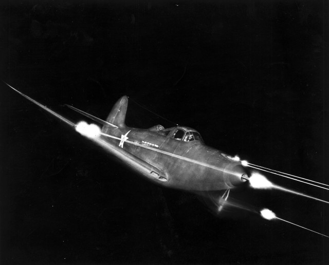 Bell P-39 Airacobra firing all weapons at night.