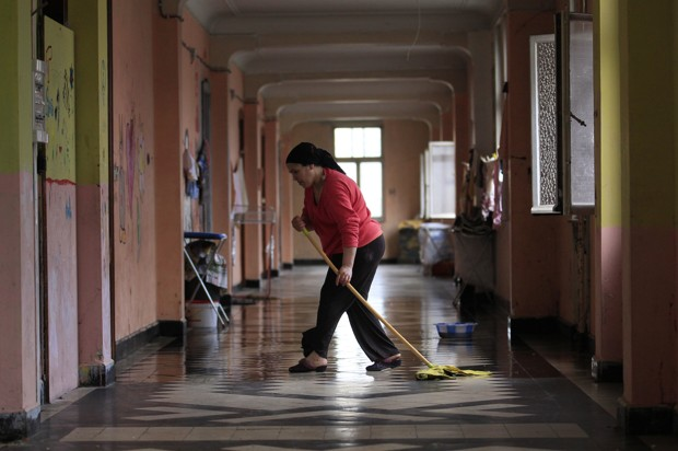 A resident cleans a corridor in the abandoned convent known as Gesu, in Brussels April 18, 2013. Some 160 squatters including 60 children may face expulsion in Brussels when a 90-million-euro project by a Swiss developer to turn their dwellings into a luxury hotel and apartments gets the go ahead. Only a few metro stops from the European institutions and the city's touristic highlights, the Gesu church and convent have remained vacant for decades and were bought by Swiss developer Rosebud Heritage in 2007, who agreed that the property could be used as a squat until the works started. Most of the residents of the squat are immigrants coming from the Czech Republic, Spain, Brazil and Morocco, looking to settle in Belgium. Some families have lived in Belgium for many years and some have stayed in the squat for months. With monthly rents at the squat currently at about 25 euros per adult, it is unlikely that the current residents will be able to move into the new apartments once they are completed. Picture taken April 18, 2013. REUTERS/Yves Herman (BELGIUM - Tags: SOCIETY POVERTY REAL ESTATE BUSINESS IMMIGRATION) - RTX118GJ