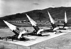 """A"" Section at SF-88L, circa 1959. The four Nike Hercules missiles are arrayed for the photographer's benefit, in a non-launching configuration. The cantonment of Fort Cronkhite is visible across the lagoon. This famous view of SF-88L was used time and time again to illustrate the Nike missile defenses of the Bay Area. U.S. Army photograph. (Golden Gate National Recreation Area, TASC Collection)"